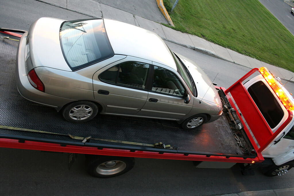 Towing a car on a flatbed Tow truck.